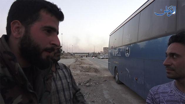 Photo of أحد ضباط الجيش السوري يحاور عدد من أهالي الغوطة الشرقية قبل التوجه إلى إدلب